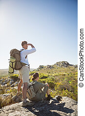 Hiking couple looking out over mountain terrain on a sunny ...