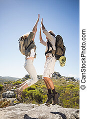 Hiking couple standing on mountain terrain cheering and ...