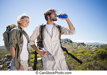 Hiking couple standing on mountain terrain taking a break
