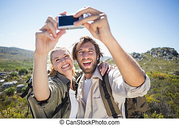 Hiking couple standing on mountain terrain taking a selfie...