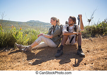 Hiking couple taking a break on mountain terrain