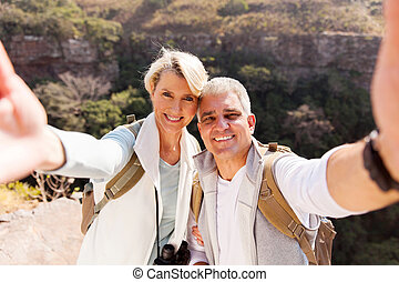 hiking couple taking selfie together - happy hiking couple...