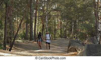 Hiking couple walks at the forest