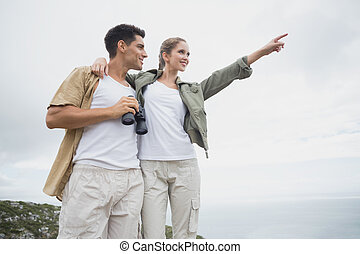 Hiking couple with binoculars on mountain terrain