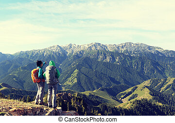 hiking friends enjoy the view on mountain top