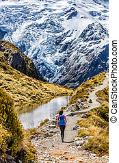 Hiking girl in New Zealand Mt Cook nature mountain. Alone hiker walking on popular trail Mueller Hut route in Mount Cook National Park mountains.