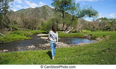 Hiking girl walking alone in beautiful landscape nature.