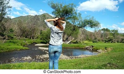 Hiking girl walking alone in beautiful landscape nature with mountains trees and a mountain river in slow motion.