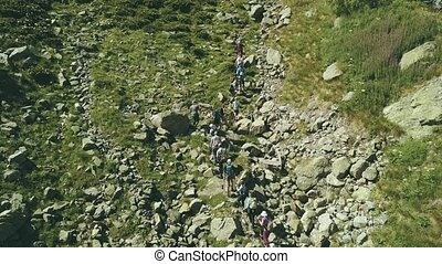 Hiking group walking on rocky trail in mountain. Climbing a...