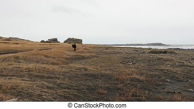 Hiking in Iceland, walking on black sand below misty cliffs...