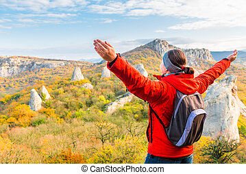 Hiking in the mountains, a traveler admiring the autumn mountains