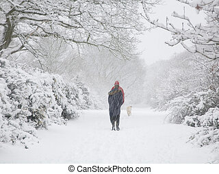 Hiking in winter - Man and woman walk in heavy snow in...