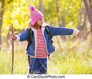 Hiking kid girl with backpack pointing finger in autumn forest