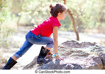 Hiking little girl climbing a rock in forest
