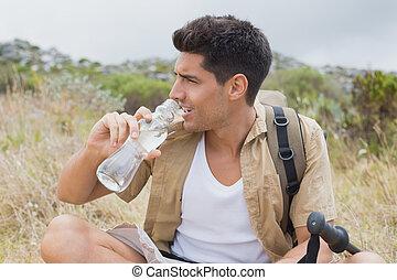 hiking, mand drik vand, på, bjerg terræn