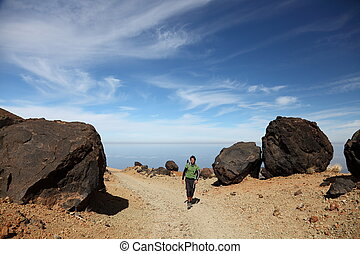 Hiking on Teide Tenerife. Man hiking / backpacking on Monta?a Blanca within the national park of Teide on Tenerife. A view of the hiking path at showing many of the big black Teide eggs or in spanish: Los Huevos del Teide. Blue sky for copy space.