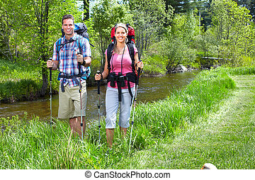 Couple with backpacks and trekking poles. Adventure.