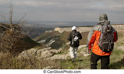 Hiking people on edge of plateau in Crimean mountains