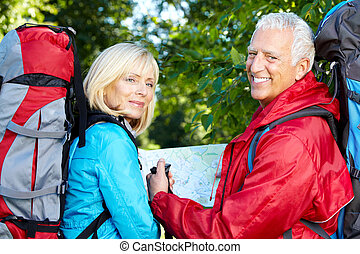 Senior couple with backpacks and trekking poles. Adventure.