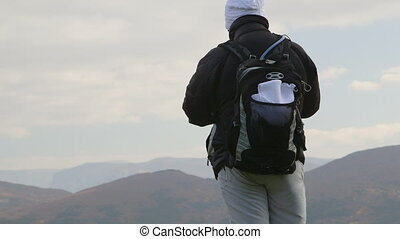 Hiking people standing with backpacks on cliff edge and looking at mountain landscape