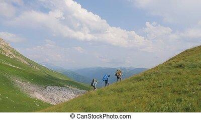 Hiking people walking on mountain on background green hills...