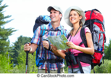Hiking people - Young couple tourists with map in the park....