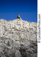 hiking - young woman resting on top of the mountain after...
