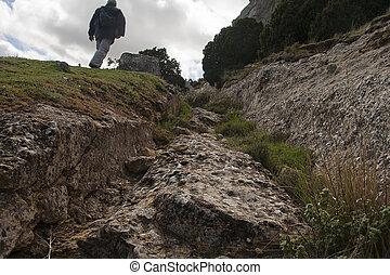 hiking ruins - hiker following iberic road ruins