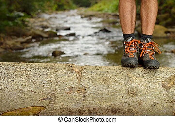 Hiking shoes legs on trunk on mountain trail. - Hiking shoes...