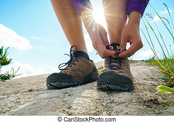 Hiking shoes - woman tying shoe laces. Closeup of female...