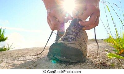 Hiking shoes - woman tying shoe laces. Closeup of female...