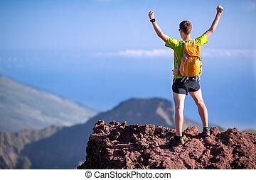 Hiking success, trail runner man in mountains