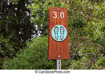 Hiking trail sign post with trees