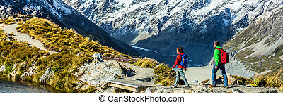 Hiking travel nature hikers in New Zealand banner. Panorama copyspace crop of tourists walking on Sealy Tarns trail and Mueller Hut route with Mount Cook background landscape.