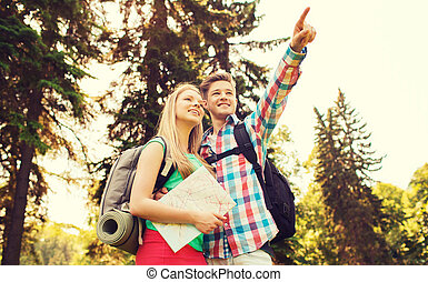smiling couple with map and backpack in nature