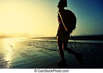 hiking woman on sunrise beach