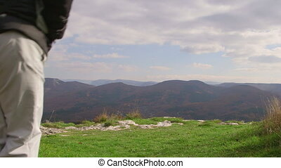 Hiking woman on the edge of plateau looking at mountain landscape