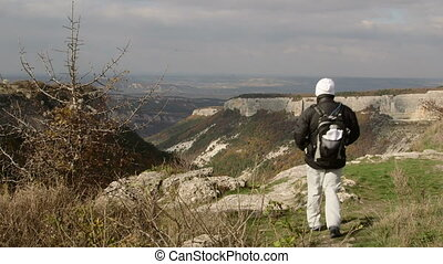 Hiking woman standing on edge of plateau with arms outstretched