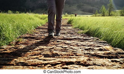 Hiking. Woman tourist walking on a bridge in the mountains. Adventure in a hike. Close-up walking legs, front view