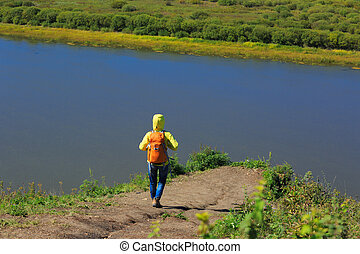 hiking woman with backpack in the  riverside mountain
