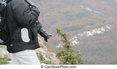 Hiking woman with camera standing on top of mountain in autumn