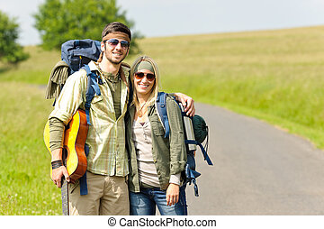Hiking young couple backpack tramping asphalt road - Hiking...