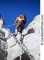 hiking - young woman reaching the top of a mountain. Copy...