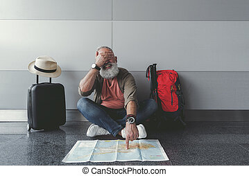 Hilarious smiling bearded man sitting in waiting hall