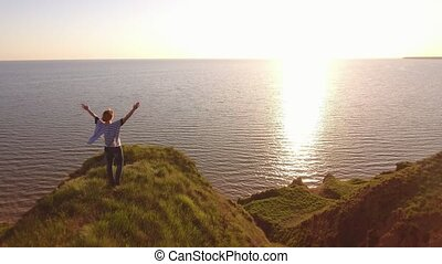 Hilarious woman raises hands standing on the Black Sea coast at sunset in summer