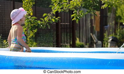 hild girl bathes in a pool under the spray of water.