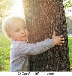 ?hild hugging a tree. Environment protection concept