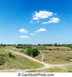 hill to river with trails under blue sky with clouds