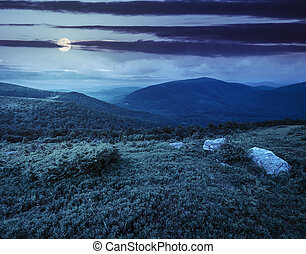 hill with white boulders in mountains at night - meadow with...