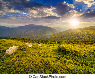 hill with white boulders in mountains at sunset - meadow...